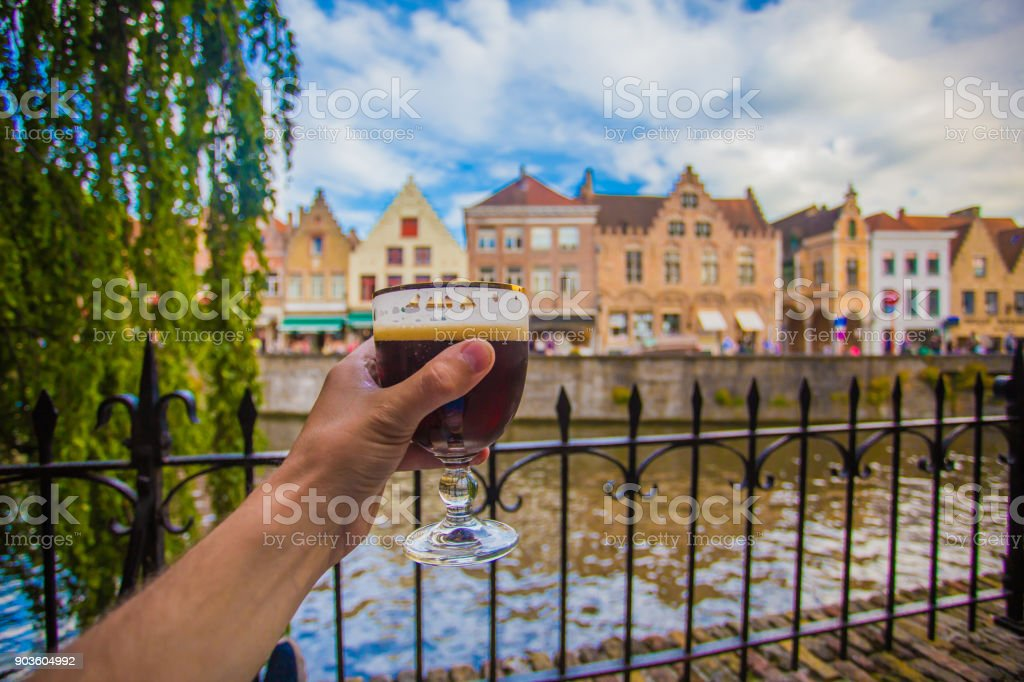 Hand with beer glass in Brugge stock photo