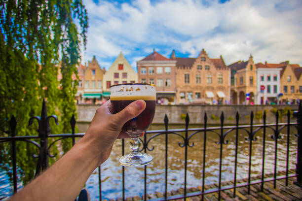 Hand with beer glass in Brugge Full glass of beer on Brugge cityscape background. Hand with beer glass in Bruges, Belgium. belgium stock pictures, royalty-free photos & images