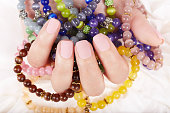 Hand with beige matte manicured nails and colorful bracelets