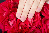 Hand with beige matte manicured nails and red rose flowers