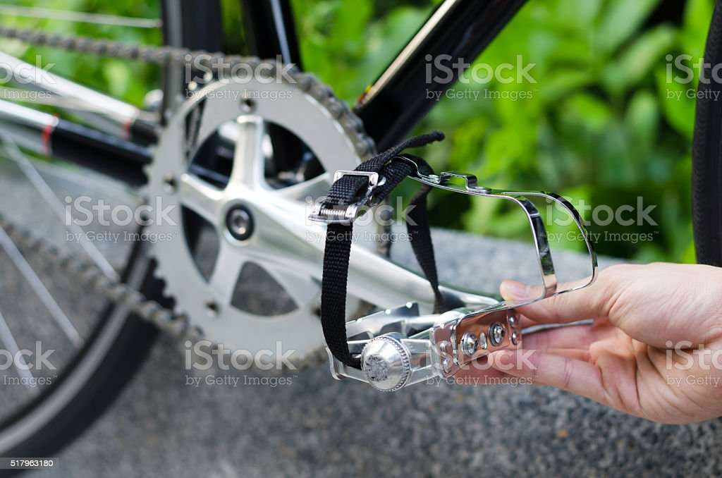 Hand with bicycle pedal stock photo