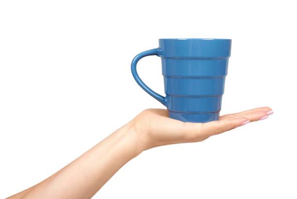 Hand met blauwe keramische Cup, mok voor koffie en thee, keuken aardewerk. foto