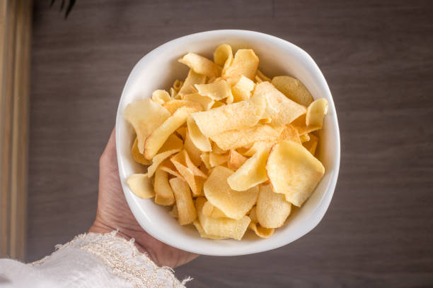 Hand with bowl with manioc chips. Hand with bowl with manioc chips. estudio stock pictures, royalty-free photos & images