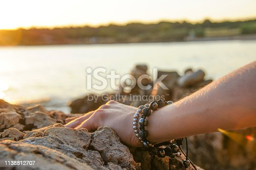 Hand with bracelets by the seaside. Sunset light.