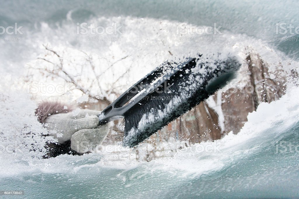 hand with brash cleaning window of car from the snow stock photo