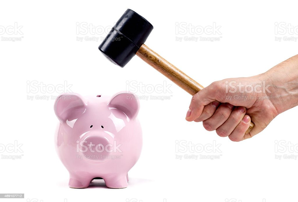 Hand with brown and black mallet poised to break piggy bank stock photo