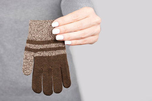 Hand with brown cotton gloves on grey