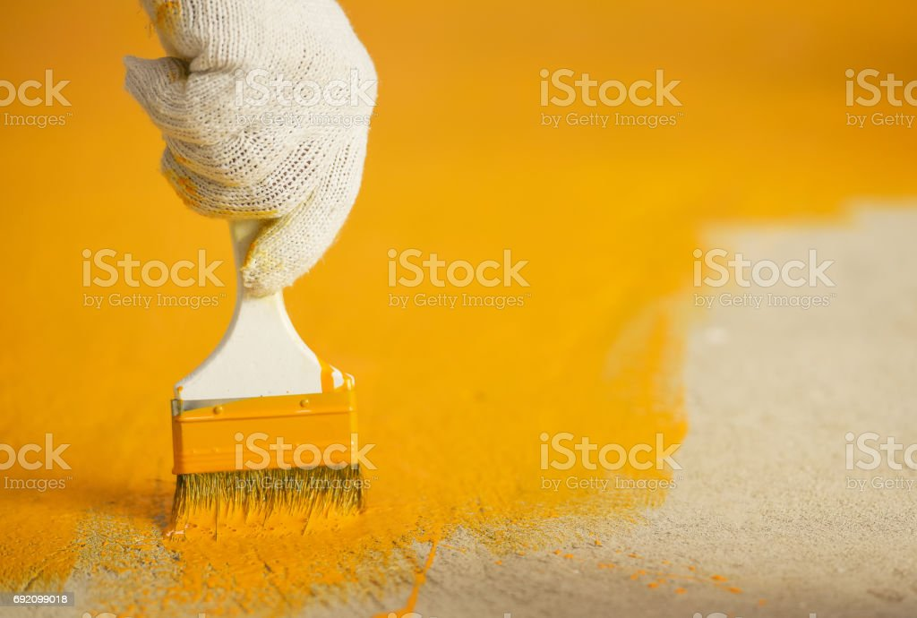 Hand with brush and yellow paint in construction site stock photo