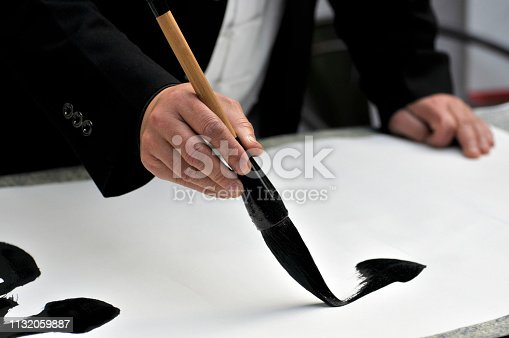 Hand with brush painting Chinese calligraphy