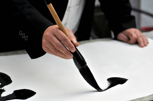 Hand with brush painting Chinese calligraphy - foto stock