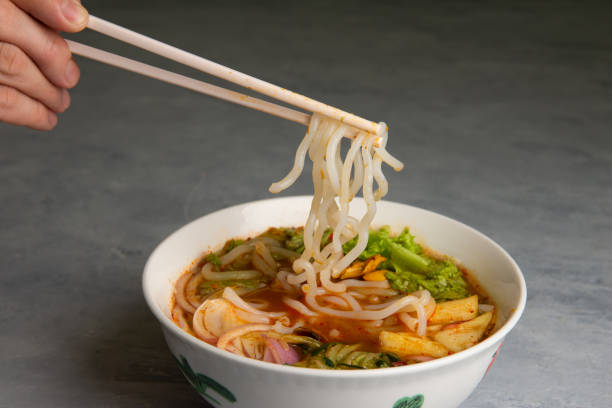 hand with chopstick and laksa curry noodles stock photo