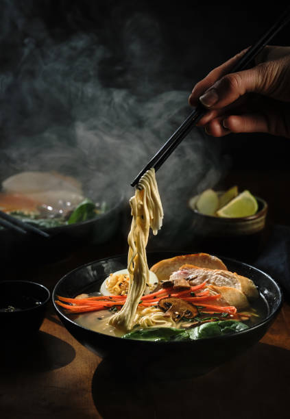 Cтоковое фото Hand with chopsticks takes noodles of ramen soup. Traditional Asian cuisine
