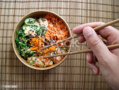 Hand with chopsticks taking food from a poke bowl