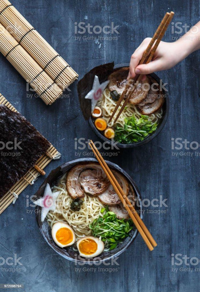 Hand with chopsticks try miso ramen stock photo