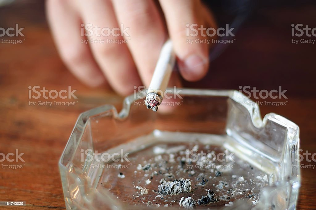 hand with cigarette and ashtray stock photo