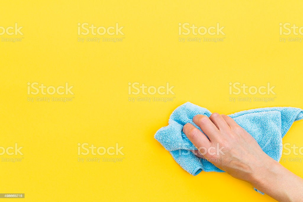 Hand with cloth cleaning surface with copy space stock photo
