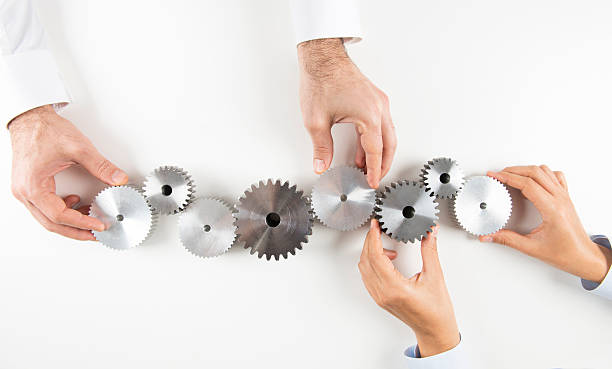hand with cogs - cog stock photos and pictures