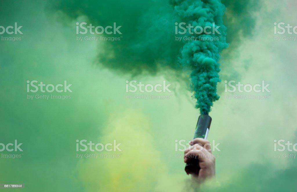 de la mano con la bomba de humo color - foto de stock