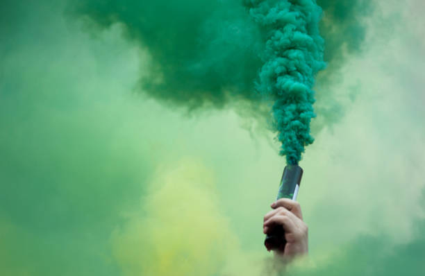 hand with color smoke bomb stock photo