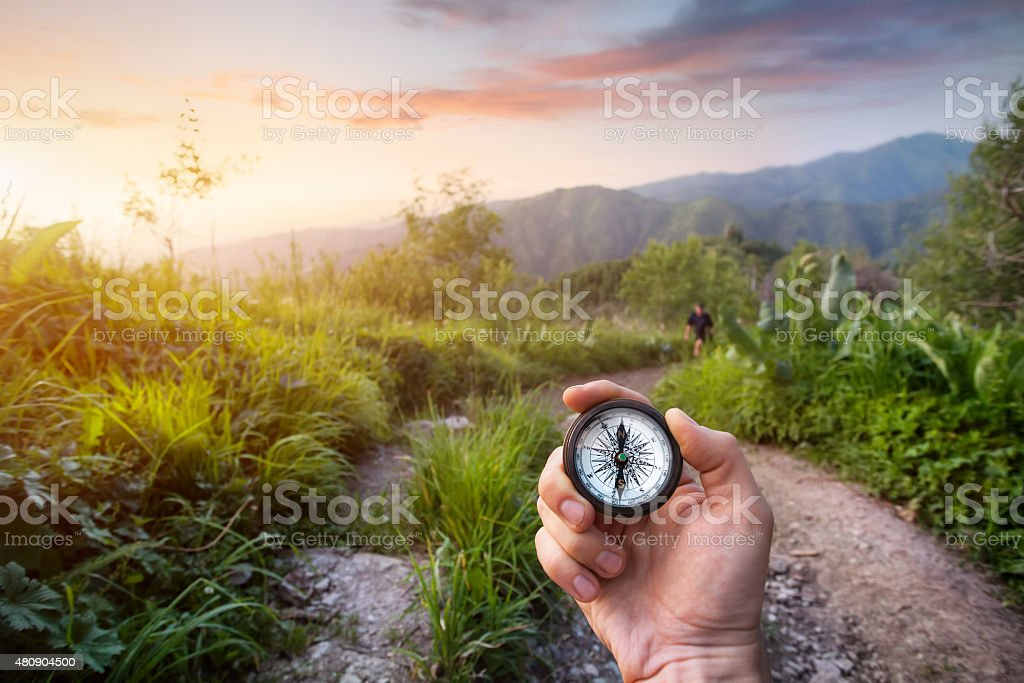 Hand with Compass in the mountains stock photo