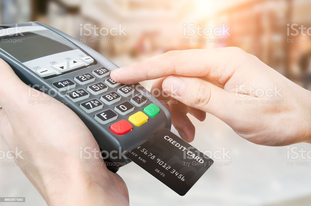 Hand with credit card swipe through terminal for sale in superma – zdjęcie
