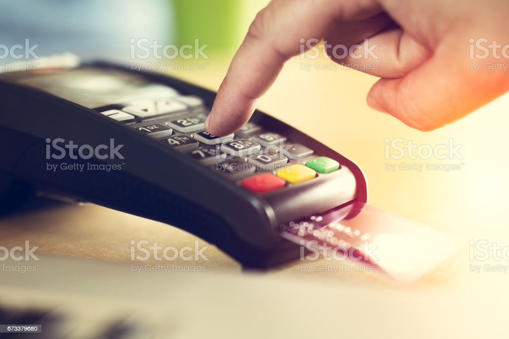 Hand with credit card swipe through terminal for sale stock photo