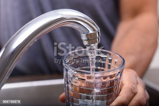 Hand with drinking glass filling water from kitchen faucet, home and lifestyle concept