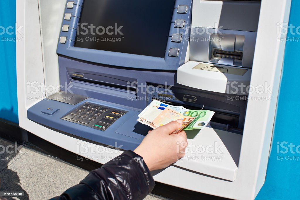 Hand with euro banknotes receives money from ATM stock photo