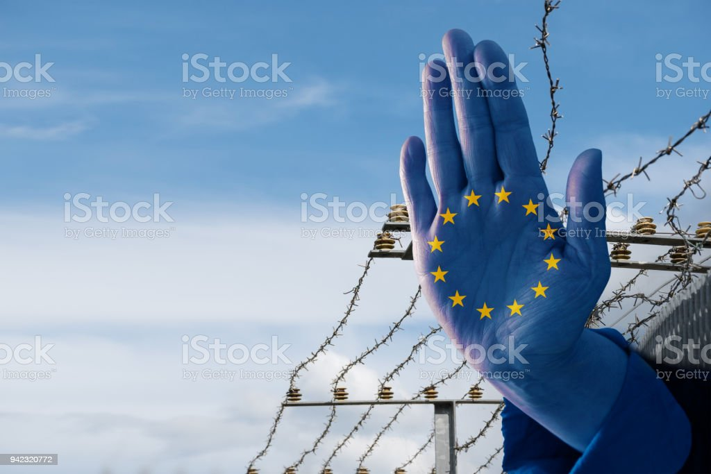 Hand with European flag stops immigration of refugees, blurred border fence in the background, blue sky with copy space stock photo