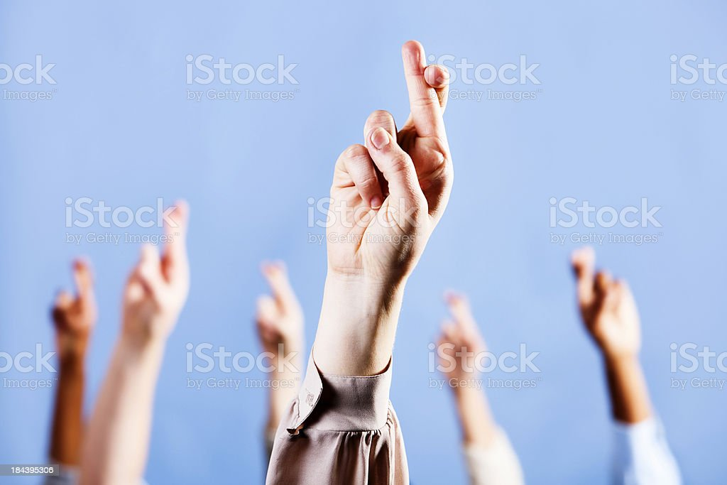 Hand, with fingers crossed for luck, backed up by others royalty-free stock photo