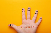 istock Hand with fingers smileys isolated on yellow background, concept of friendship. 1222190557