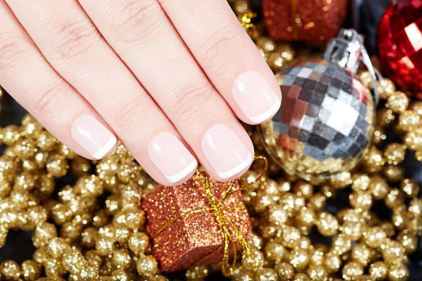 hand with french manicured nails and christmas decorations - nageldesign weihnachten stock-fotos und bilder