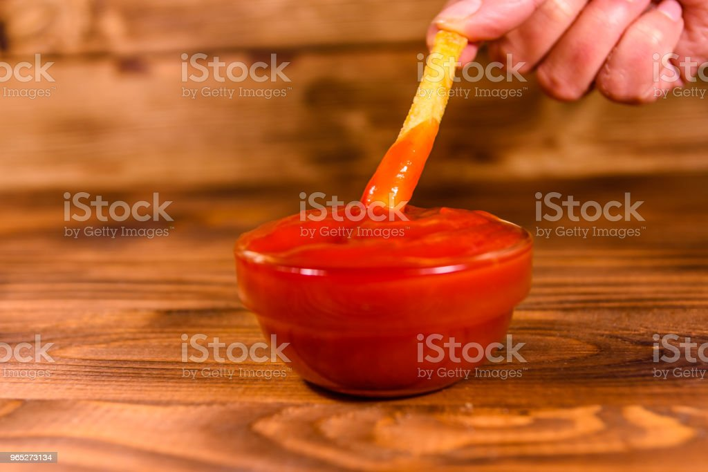 Hand with fresh french fry dipped into the tomato sauce zbiór zdjęć royalty-free