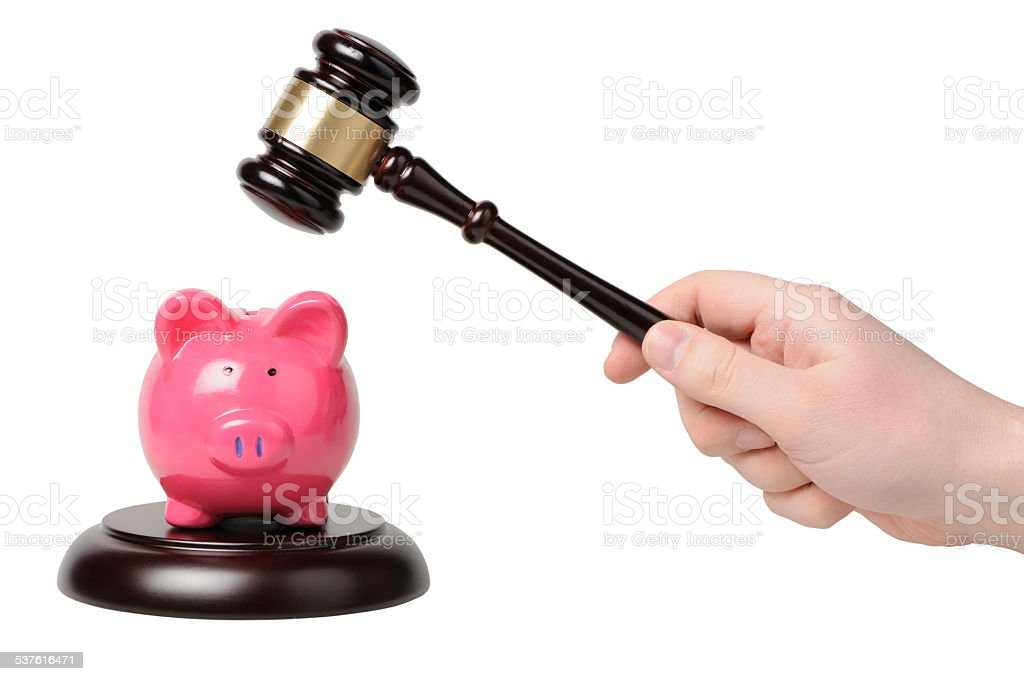 Hand with gavel beats on a piggy bank stock photo