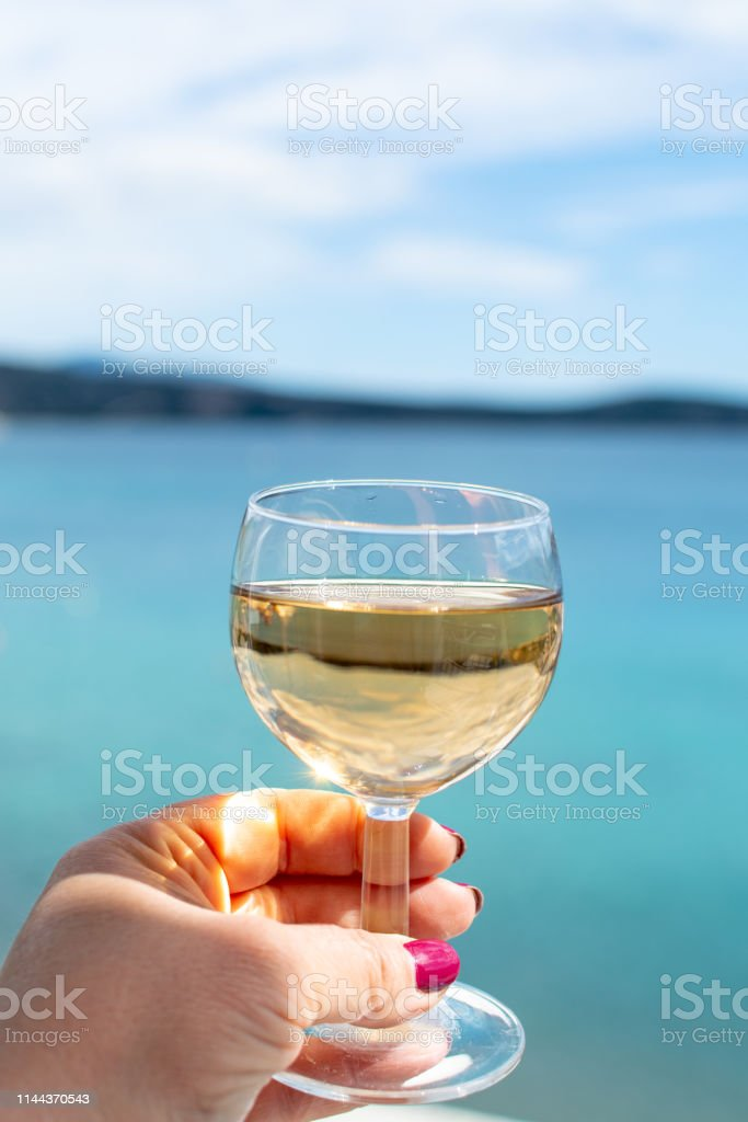 hand with glass of white wine served outside on balcony with sea view...