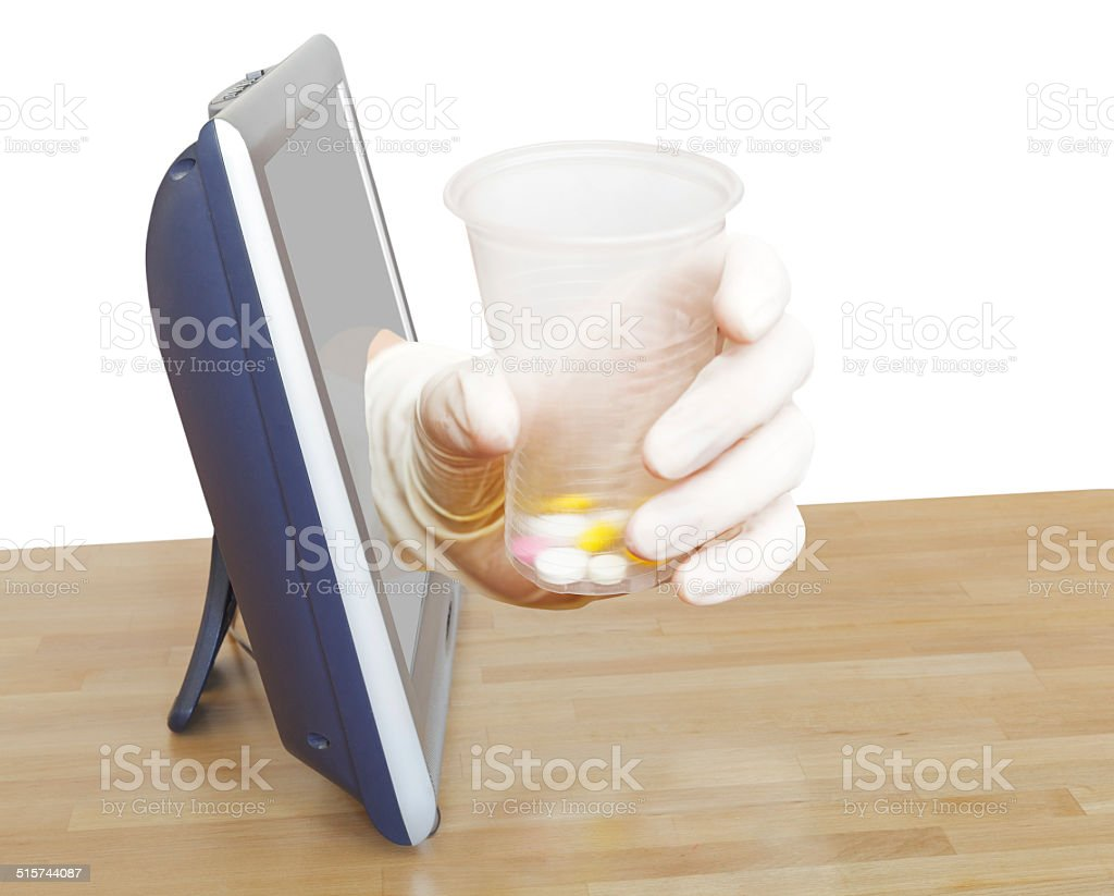 hand with glass with pills leans out TV screen stock photo