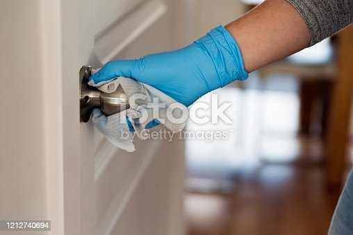 Female hand with blue glove wiping doorknob with disinfectant wipe. Horizontal indoors close-up with copy space.