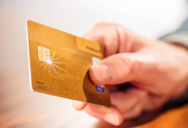 Hand mit goldener Kreditkarte Nahaufnahme einer Hand mit einer goldenen Kreditkarte credit card purchase stock pictures, royalty-free photos & images