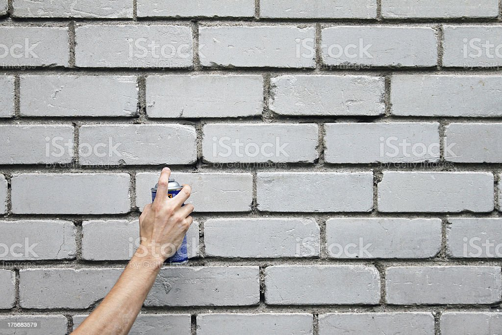 hand with graffiti spray can in front of blank wall royalty-free stock photo