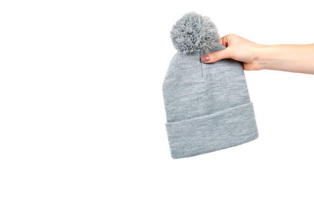 Hand met grijze gebreide muts, warme wollen accessoire. foto
