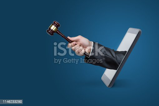 istock Hand with hammer coming out of a phone . 1146233250