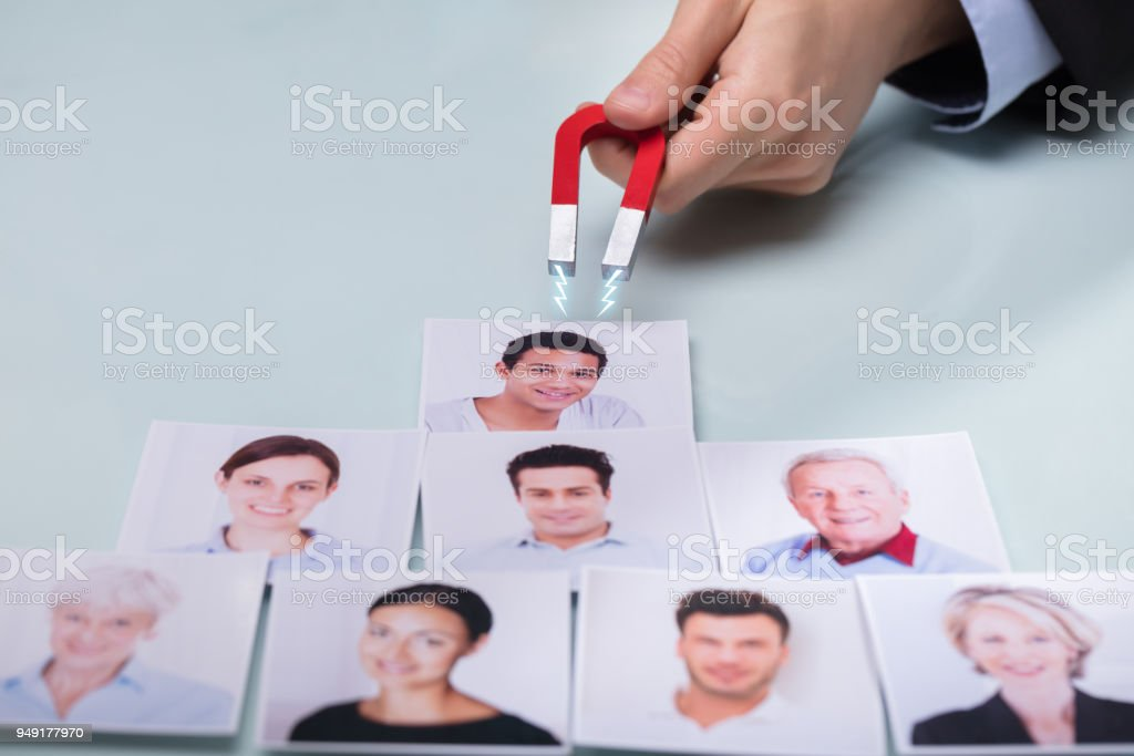 Hand With Horseshoe Magnet Attracting Photographs stock photo