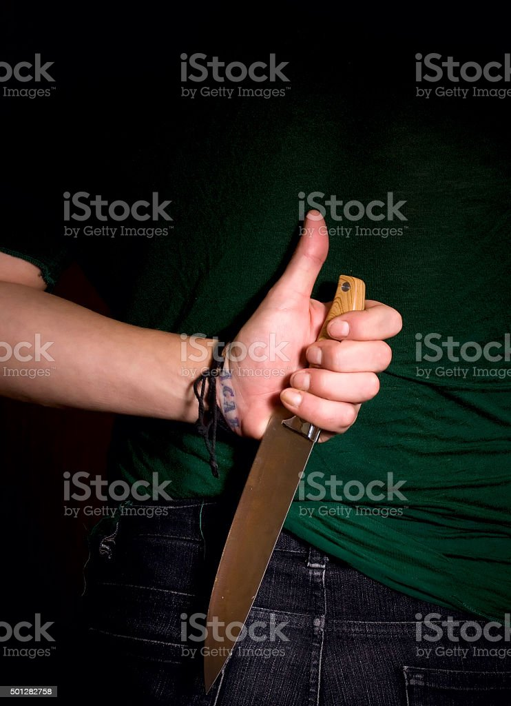 hand with knife behind his back stock photo