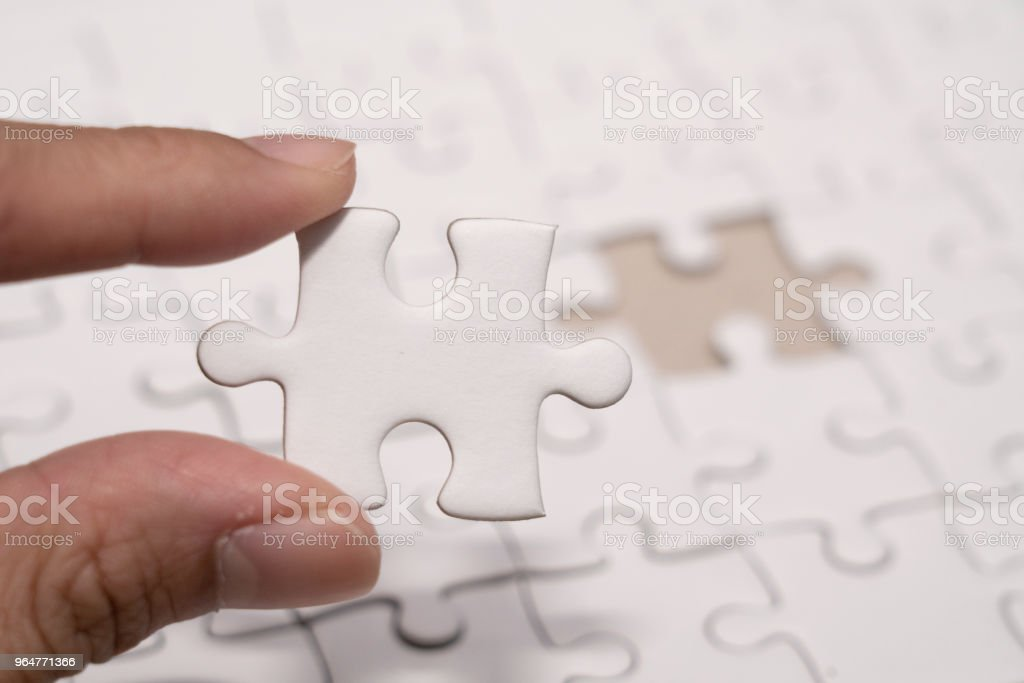 hand with last piece of Jigsaw puzzles with blank copyspace royalty-free stock photo