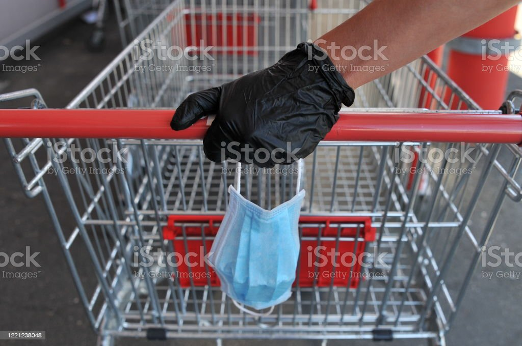 Hand with latex gloves holds face mask and shopping cart Hand with latex gloves holds face mask and shopping cart during corona crisis Bacterium Stock Photo