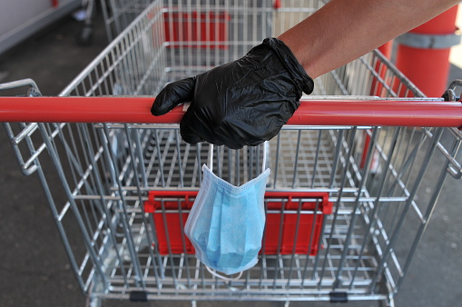 Hand With Latex Gloves Holds Face Mask And Shopping Cart Stock Photo - Download Image Now