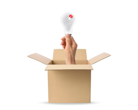 istock Hand with light bulb protruding from cardboard box 1130415358