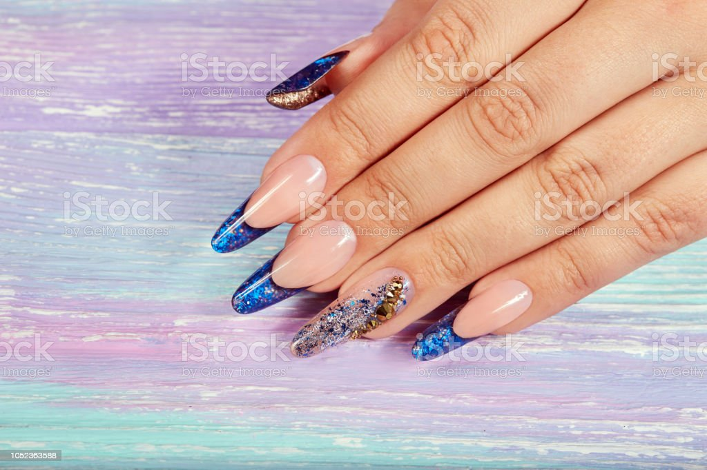 Hand with long artificial blue french manicured nails decorated with...