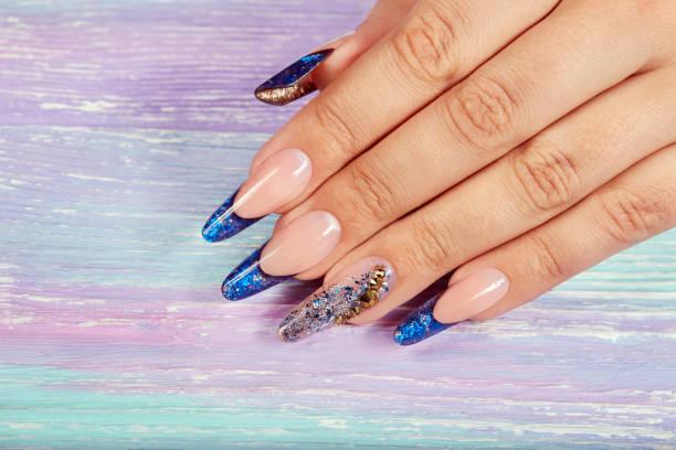 hand mit langen künstlichen blauen französischen gepflegten nägeln - gelnägel stock-fotos und bilder