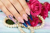 フランス長い人工爪とピンクのバラの花の手